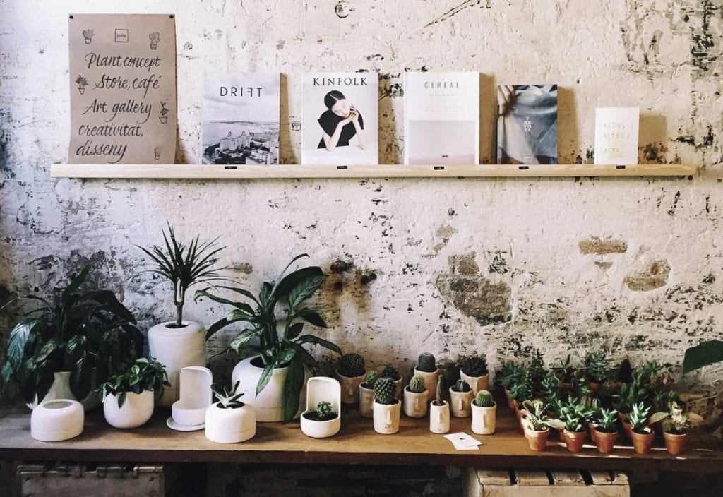 Espai Joliu wall with indie magazines and plants