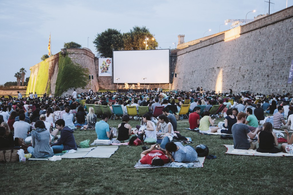 People sitting on the grass at Montjuïc Castle open-air cinema at evening